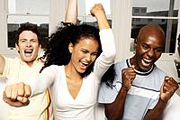 Young woman and two men cheering on sofa, arms raised, close_up