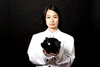 Young woman wearing a white suit holding piggy bank, portrait