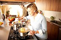 Mature man and woman preparing food in domestic kitchen, side view