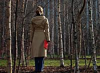 Woman standing in woods, holding red book, rear view