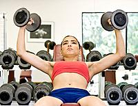Young woman weight training in gym