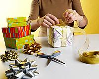 Woman´s hands tying bow on wrapped present