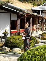 Japan, Kyoto, Enko Temple, woman in kimono walking in garden outside temple