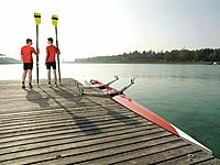 Two teenage rowers 16_17 holding oars, standing on pier looking at each other