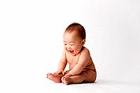 Naked baby boy on white background, laughing