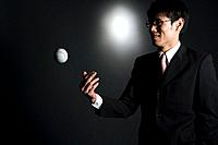Businessman throwing baseball, studio shot