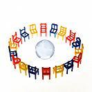 Colourful chairs surrounding glass globe, studio shot