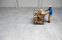 Male employee pushing trolley of packages inside courier depot
