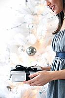 Young woman holding wrapped gift in front of Christmas tree