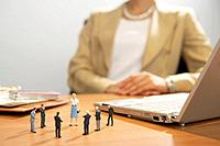 Group of businessman figurines on desk, out of focus woman sitting behind