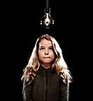 Girl standing beneath a lightbulb.