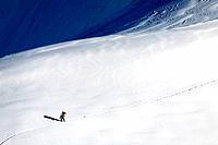 Lone skier near the Aiguille du Midi cable car station, Les Bossons, Chamonix Mont Blanc, Rhone-Alpes, France
