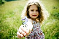 Girl holding flower to camera