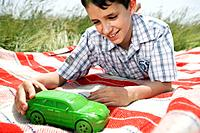 Boy playing with green toy car