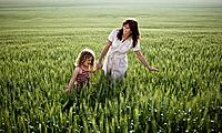 Woman and child walking in wheat_field