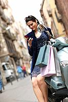 Young woman with shopping bags & mobile