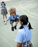 School boy skipping rope