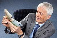 Businessman with lots of money in hands (thumbnail)