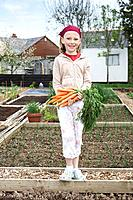 Girl on allotment with carrots