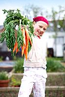 Girl on allotment with carrots (thumbnail)