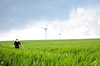 Pregnant woman walking through wind farm