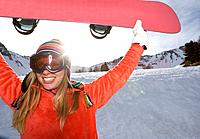 Girl lifting ski board, smiling