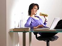 Woman at her desk, eating