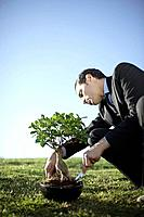 Business man nurturing bonsai outdoors (thumbnail)