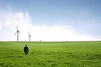 Man walking towards wind turbines