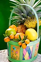 Basket with tropical fruits: pineapple, lemons, limes, tangerines, kumquat and Protea flower