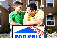Father and Son Leaning on a Sold Sign
