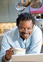 African man drinking coffee in kitchen