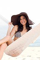 Cuban woman wearing hat in hammock on beach
