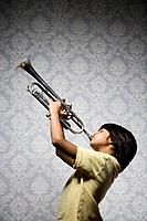 Mixed race boy playing trumpet