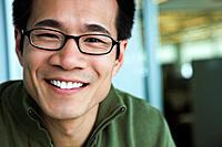 Close up of Asian American man wearing eyeglasses and smiling