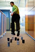 Indian businessman running from cell phones on office floor