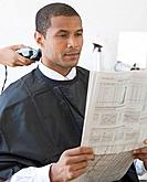 African man reading paper at barbershop