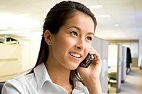 Eurasian businesswoman talking on cell phone in office