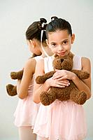 Hispanic girl ballerina hugging teddy bear