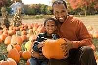 African father and son holding pumpkin at pumpkin patch