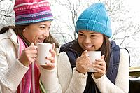 Multi_ethnic girls in snow drinking hot cocoa