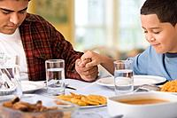Hispanic father and son praying at dinner table