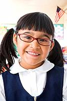 Close up of Hispanic girl wearing eyeglasses in classroom