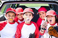Multi_ethnic boys in baseball uniforms making faces and holding trophy