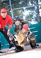 Multi_ethnic baseball catcher and coach behind home plate