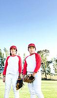 Multi_ethnic boys in baseball uniforms looking pensive