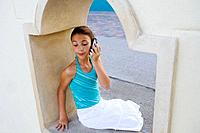 pre-teen talking on cell phone at beach
