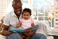 African father reading story to daughter in bedroom