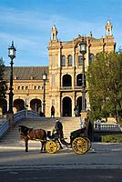 A driver pauses his carriage while his passengers explore the Plaza de Espana in Maria Luisa Park, Seville, Spain, Europe  The building was designed b...