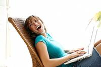 Girl using laptop computer and laughing